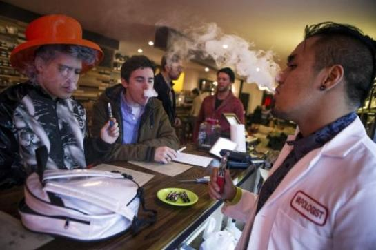 1 OF 3. An employee 'Vapologist' (R) stands behind the bar as he puffs on an e-cigarette with customers at the Henley Vaporium in New York City in this December 18, 2013 file photo. CREDIT: REUTERS/MIKE SEGAR/FILES