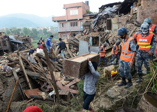 People carry their belongings amid the rubble of collapsed houses in Bhaktapur, on the outskirts of Kathmandu, on April 27, 2015. Prakash Mathema / AFP / Getty Images