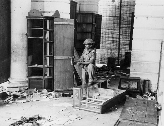 A lone soldier on guard at a looted stall in a Delhi street following a riot, Sept. 16, 1947.