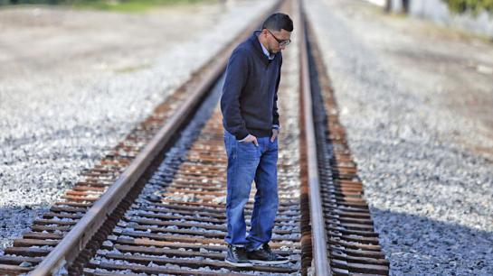Kris Ramiriez stands on the railroad tracks in Paramount near where his brother, Oscar Ramirez, was killed by deputies in October.  (Mark Boster / Los Angeles Times)
