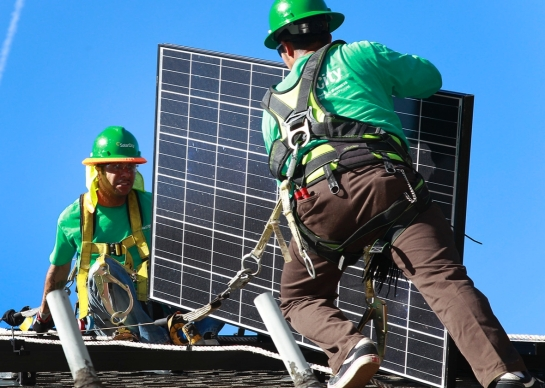 Lead installers for SolarCity, Charles Groves, right, and Matt Parra, install solar panels on the roof of a home on March 31, 2011, in Palo Alto, California. Photo by Tony Avelar/The Christian Science Monitor via Getty Images