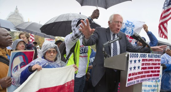 Democratic presidential candidate Sen. Bernie Sanders joins low-wage workers, some who labor as cooks and cleaners at the Capitol, as he speaks during a rally. | AP Photo
