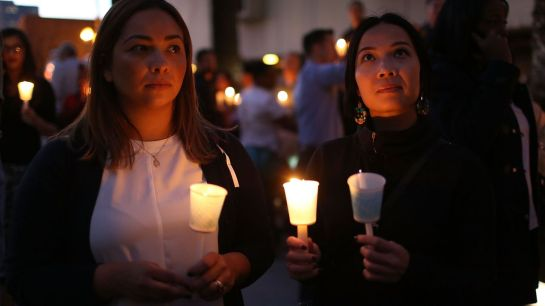 People hold candles at a San Bernardino vigil for attack victims.		Joe Raedle/Getty