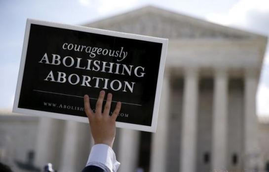 An anti-abortion protester with a group celebrating the U.S. Supreme Court's ruling striking down a Massachusetts law that mandated a protective buffer zone around abortion clinics, holds up a sign outside the Court in Washington, in this June 26, 2014 file photo. REUTERS/Jim Bourg/Files