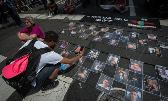 Photographs of the victims of the Orlando Pulse nightclub shooting are laid out prior to the start of the 46th annual Gay Pride march June 26, 2016 in New York. New York kicked off June 26 what organizers hope will be the city's largest ever Gay Pride march, honoring the 49 people killed in the Orlando nightclub massacre and celebrate tolerance. / AFP / the 46th / Bryan R. Smith    --    (Photo credit should read BRYAN R. SMITH/AFP/Getty Images)