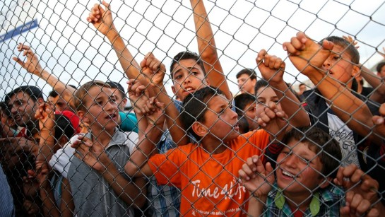 Syrian refugee children chant slogans behind a fence at the Nizip refugee camp in Gaziantep province, southeastern Turkey, following a visit by German Chancellor Angela Merkel and top European Union officials, Saturday, April 23, 2016 -- CREDIT: AP PHOTO/LEFTERIS PITARAKIS