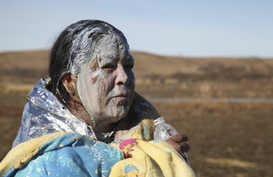 Tonya Stands recovers from being pepper sprayed by police after swimming across a creek with other protesters hoping to block construction of the Dakota Access Pipeline, near Cannon Ball, N.D., on November 2.| John L. Mone/AP