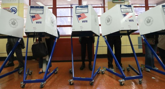 Voters cast their ballots in booths at The Straus School on in New York on Nov. 8. | Getty
